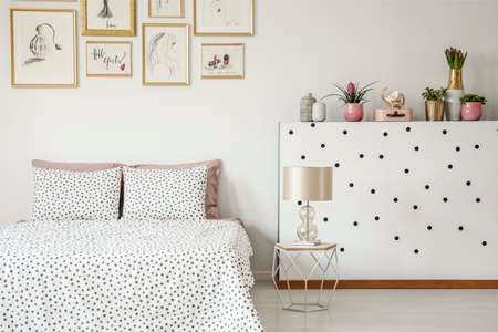Elegant lamp on a diamond shape nightstand by a white wall with polka dot stickers and plants in a bright bedroom interior with golden and pink decorations
