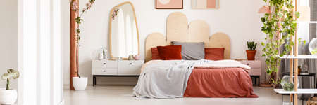 Bright bedroom interior with king-size bed with grey and red bedding, white cupboard with decorations, mirror hanging on the wall and plants