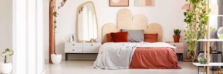Intérieur de chambre lumineux avec lit king-size avec literie grise et rouge, armoire blanche avec décorations, miroir accroché au mur et plantes Banque d'images