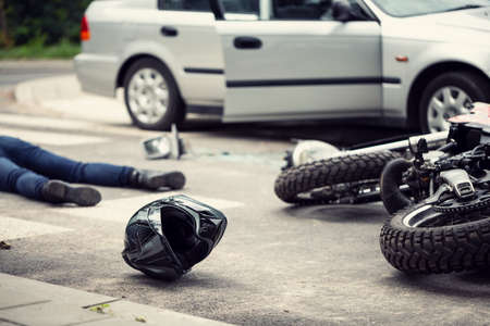Black helmet and motorcycle after dangerous traffic incident with car on the street 스톡 콘텐츠 - 104388425