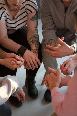 Jóvenes con tatuajes sentados en círculo durante la reunión del grupo de apoyo Foto de archivo