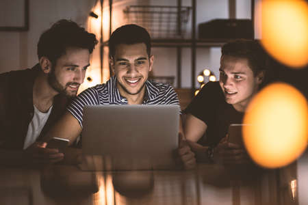 Group of smiling friends using laptop and uploading photos on social media