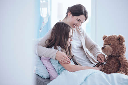 Smiling mother and weak daughter taking care of teddy bear in the clinic Stockfoto