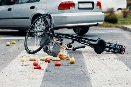 A broken bike on a pedestrian crossing after a collision with a car