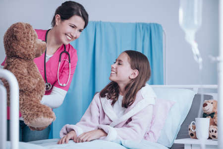 Smiling doctor in pink uniform giving plush toy to happy sick child in the health center