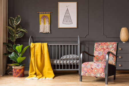Patterned armchair next to kids bed with yellow blanket in bedroom interior with plants. Real photo Stockfoto