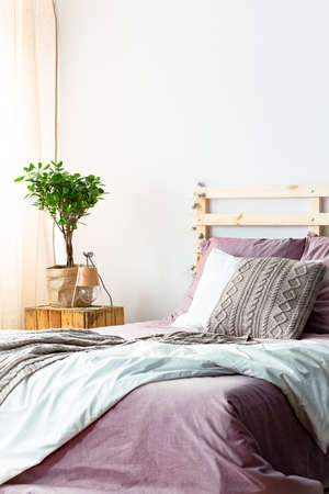 Handmade lamp and fresh plant standing on wooden bedside table next to bed with purple sheets and knit pillow in bright bedroom interior