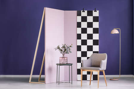 Partition wall with checkered pattern set in a purple room interior with an armchair, table and plant in front