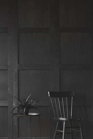 Black chair next to table with plant in monochromatic room interior. Real photo
