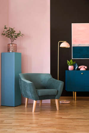 Green armchair in colorful living room interior with pink phone on navy blue cabinet