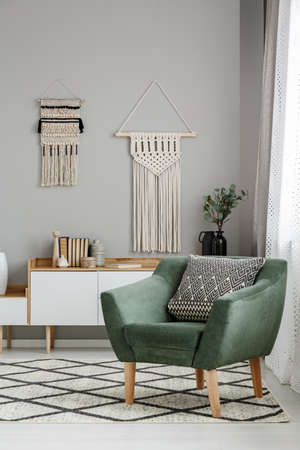 Real photo of a boho living room interior with macrame hanging on gray wall behind a comfy, green armchair with a cushion 写真素材