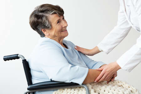 Caregiver supporting happy disabled senior woman in a wheelchair Banque d'images - 104450388