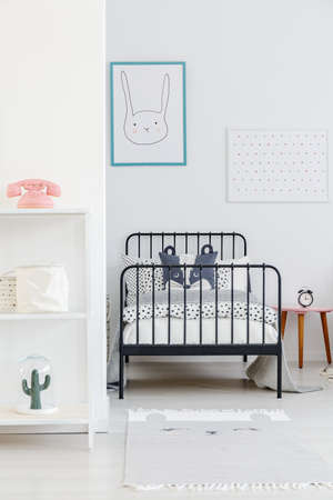 Child's bed with black metal frame in a small, simple bedroom interior. Rabbit poster on a white wall. Real photo Archivio Fotografico