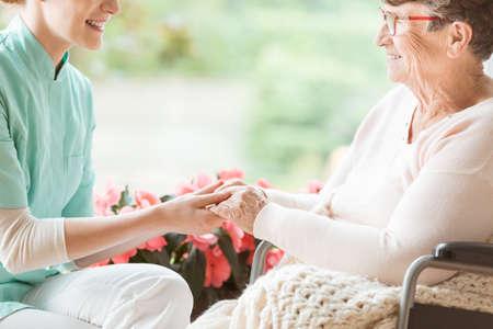 Enfermera preparando a un pensionista discapacitado para dar un paseo por el jardín de la casa de retiro