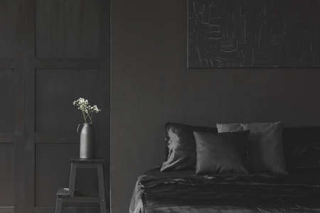 White flowers on stool next to bed with cushion in black bedroom interior. Real photo Stock Photo