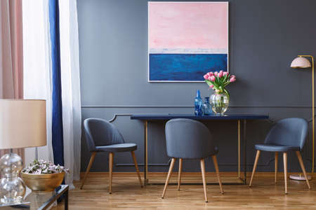 Pink flowers on table in dining room interior with painting and grey chairs next to lamp. Real photo