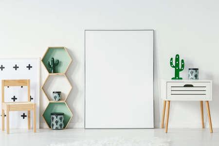 Piccolo armadio con lampada a forma di cactus e scatola decorativa in piedi all'interno della cameretta bianca con poster vuoto con posto per la tua sedia grafica, in legno e ripiani geometrici