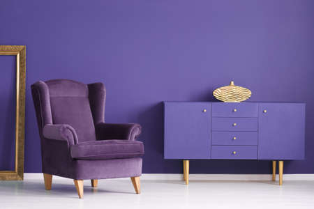 Purple cabinet with a golden vase, comfy armchair and frame in a living room interior