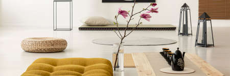 Pink flowers and pouf next to wooden desk on the floor in japanese interior. Real photo Zdjęcie Seryjne