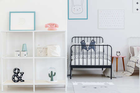 Kids bedroom interior with a view of one whole bed and a part of the other. Shelves with decorations and posters on the white wall. Real photo