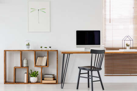 Real photo of a computer with empty screen standing on a wooden desk in bright freelancer's office interior with black chair and bookcase Banco de Imagens
