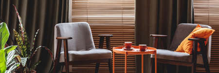 Two grey armchairs, orange end table and tea cups in sitting room interior with windows with blinds and curtains Stock Photo