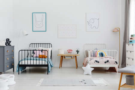 Cozy bedroom interior for siblings. Two beds, one white, one black with patterned bedding and posters of a rabbit and elephant on the wall. Real photo