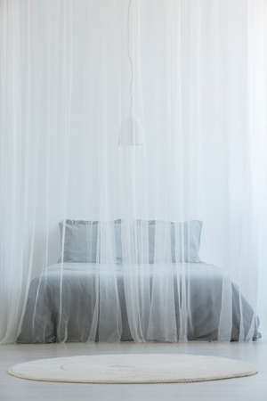 Mosquito net bed with grey bedding standing in white room interior with round rug on the floor Zdjęcie Seryjne