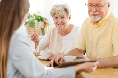 Smiling senior woman and husband talking to a financial advisor about a loan Stock Photo