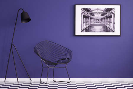 Modern chair, black lamp, checkered floor and painting on a purple wall in living room interior