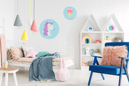 Furry pink pillow on a vibrant blue armchair in a sweet kid bedroom interior with cozy bedding and cartoon posters on white walls Foto de archivo - 104454774