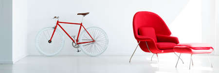 Red bicycle in white living room interior with modern armchair with stool. Real photo
