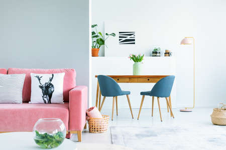 Pillows on pink couch in bright interior with blue chairs at dining table with flowers. Real photo