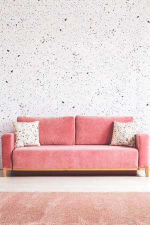 Patterned cushions on pink sofa in living room interior with carpet and lastrico wallpaper. Real photo