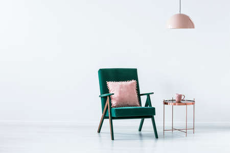 Pink pillow on green armchair next to a copper table in white simple interior with copy space