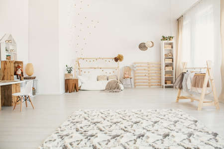 Fluffy carpet in white kid bedroom interior with house-shaped bed, windows with drapes, rack with boxes and small wooden hanger