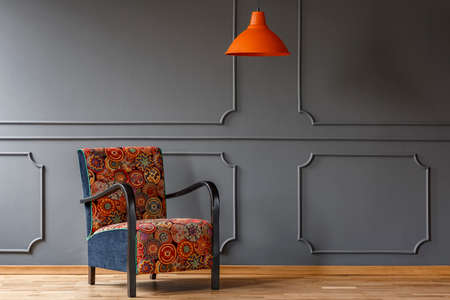 Orange lamp above patterned armchair in modern grey living room interior. Real photo Stock Photo