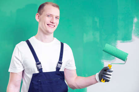 Smiling handyman with roller painting the wall green while finishing interior Stok Fotoğraf