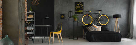 Dark studio flat interior with textured grey wall, black and yellow bike standing on bedhead, desk with geometric chair and double bed with black bedding Banque d'images