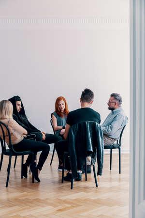Adolescentes rebeldes y psicólogo sentados en círculo durante la terapia de grupo Foto de archivo