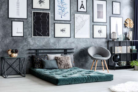 Grey armchair next to green futon in modern living room interior with posters