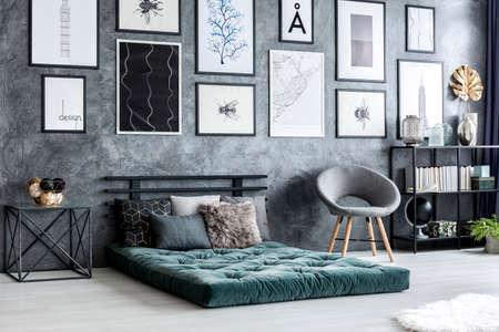 Fauteuil gris à côté de futon vert dans l'intérieur du salon moderne avec des affiches