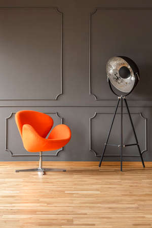 Orange armchair next to lamp in grey living room interior with wooden floor. Real photo Stock Photo