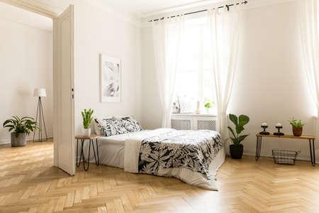 Plant op tafel naast bed in wit open ruimte interieur met raam en poster. Echte foto