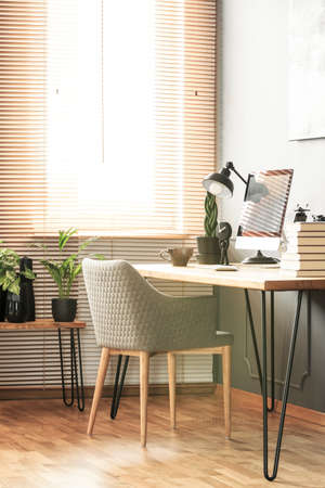 Grey armchair at desk with desktop computer and lamp in bright workspace interior. Real photo 版權商用圖片