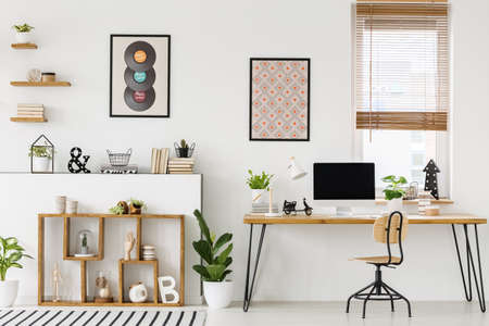 Real photo of a desk with a computer screen standing with a chair next to shelves with ornaments in a bright workplace interior with posters on a wall and window with blinds