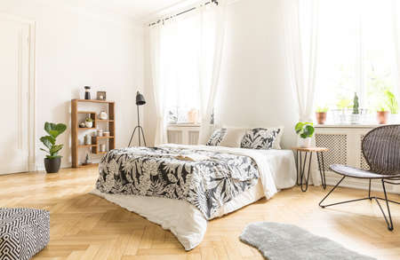 Black chair near bed with patterned sheets in white bedroom interior..