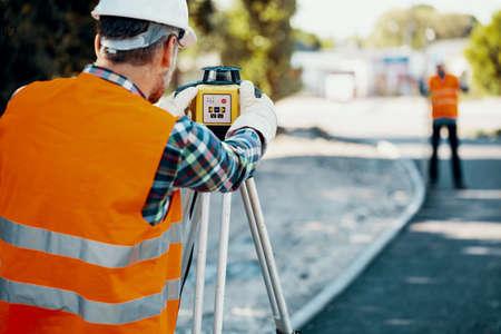 Engineer in orange reflective vest using professional equipment during carriageway work Stock Photo