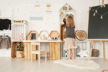 Little girl organizing her toys in white Nordic style bedroom interior with posters, wooden furniture, fluffy rug and blackboard with lights Stockfoto