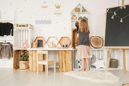 Niña organizando sus juguetes en el interior del dormitorio de estilo nórdico blanco con carteles, muebles de madera, alfombra mullida y pizarra con luces